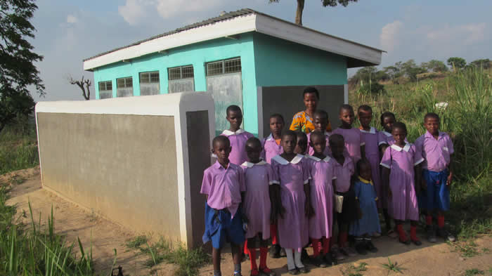 Sanitation and Senior Woman Teacher, Ms. Kasande Anah with School Sanitation Club members pose for a photo at the new VIP latrine at Maberenga Primary School